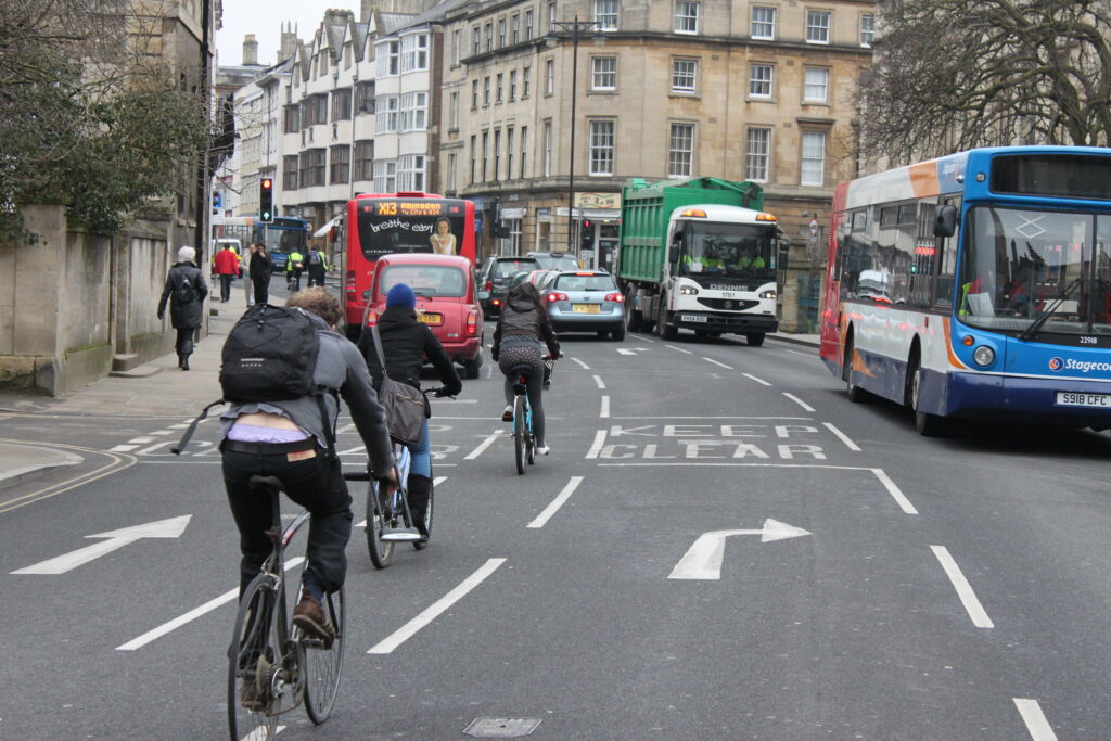 Three people cycling in the cycle lane filter on Magdalen Bridge, Oxford, in the direction of the High Street to turn right onto Longwall Street. The road is shared by busses, cars and a lorry.