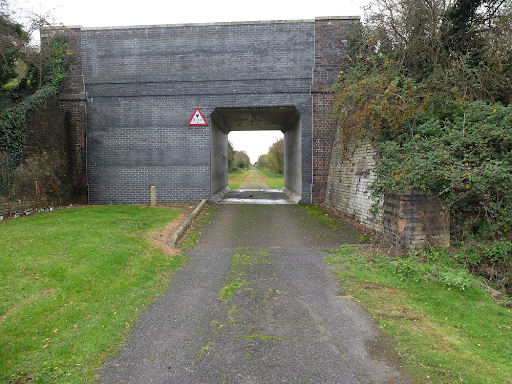 A disused gravel track going under a bridge, green grass growing either side.