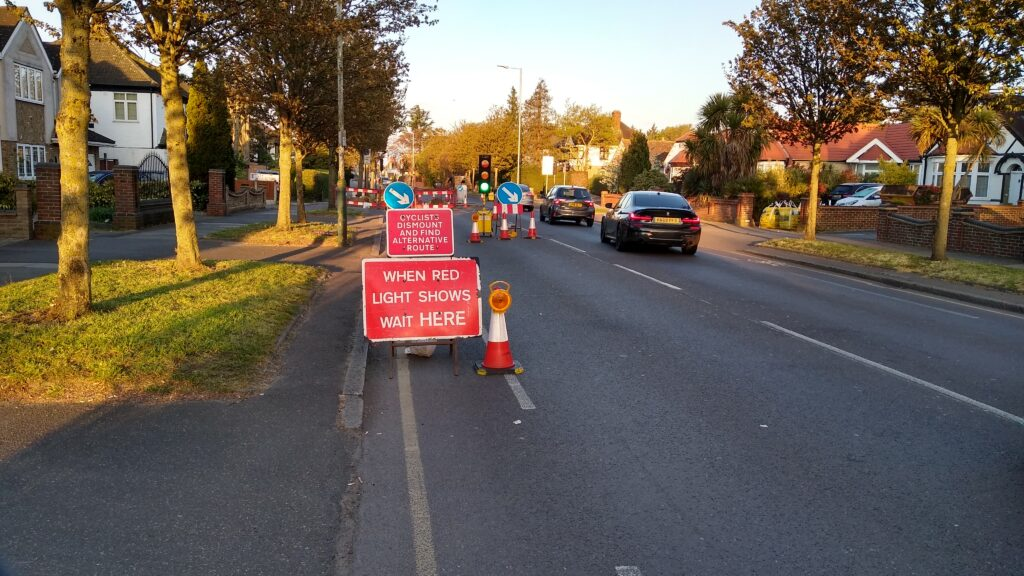 Roadwork signs block the painted cycle lane at a set of temporary traffic lights on a wide road. A smaller red sign above a larger red sign advising the traffic to stop when the light shows red says: 'cyclists's dismount and find an alternative route'.